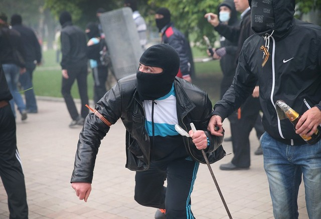 DONETSK, UKRAINE - APRIL 28:  A pro-Russian activist throws a projectile during a violent clash with pro-government supporters during a rally and march on April 28, 2014 in Donetsk, Ukraine. Several people were injured when the pro-Russian activists attacked a pro-government march.  (Photo by Scott Olson/Getty Images)