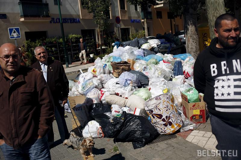 People stand next to a pile of rubbish bags as they watch as workers contracted by the town hall, remove rubbish bags in a street during a strike by garbage collectors from waste management company Limasa in Malaga